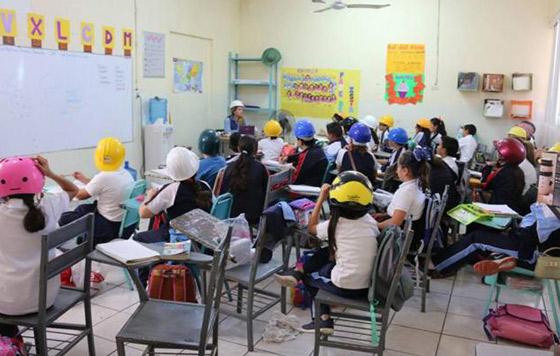Niños acuden con casco a la escuela, temen se caiga el techo