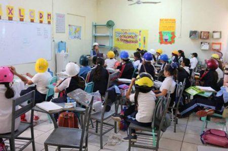 Van a la escuela con cascos por aulas en mal estado