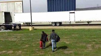Familia migrante cruza la frontera frente a los muros de Trump